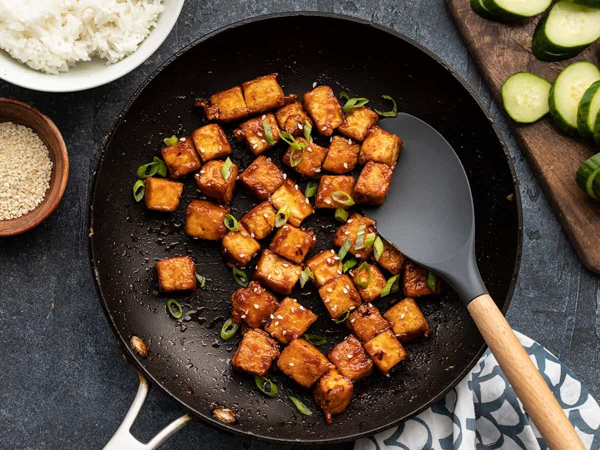 Honey sriracha tofu in the skillet with a spatula, ingredients on the sides